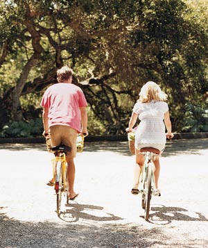 A man and a woman biking in the countryside
