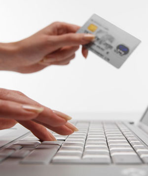 Woman using laptop computer, holding credit card