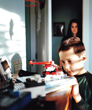 Boy with toy stands at dresser mother watches from background