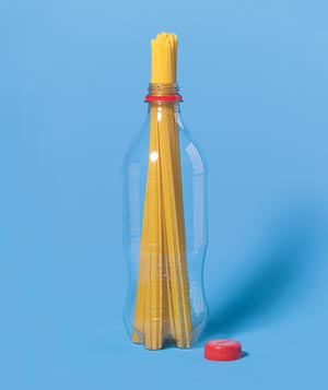 Clear plastic soda bottle holding dry pasta