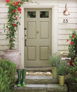 Cottage doorway with green door and red flowers