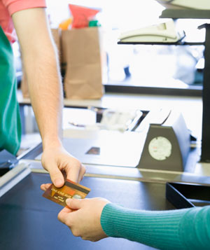 Woman paying at cashier with credit card, close-up of arms