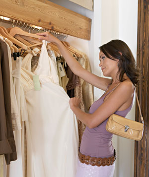 Woman browsing rails of clothes in shop