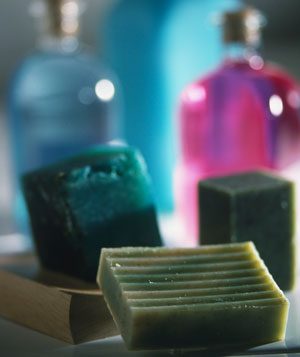 Selection of green soaps, blue and pink bottles in background
