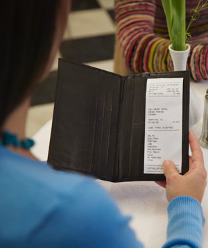 Woman checking bill in restaurant
