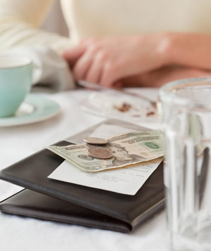 Woman leaving tip on restaraunt bill