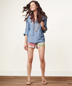 Model wearing blue Talbots tunic, floral Loft shorts, gold sandals and gold Yochi necklace