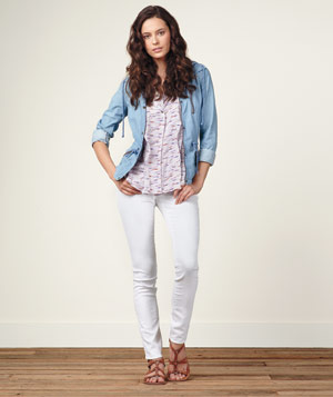 Model wearing white Express jeans, denim jacket, print blouse and gladiator sandals