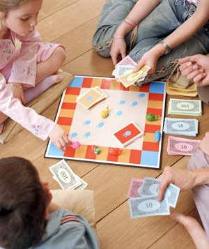Children and parents playing board game together on floor