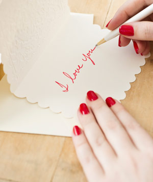 Hands writing I Love You on a card