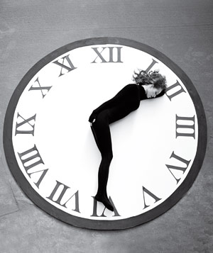 Black and white photography of giant clock with woman in black lying on it in the shape of clock arms