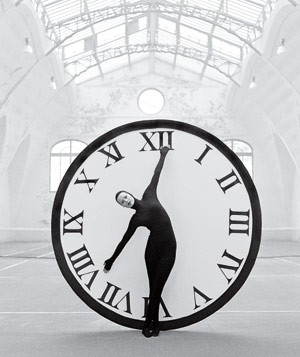 Black and white photograph of a woman in a black catsuit making arms of clock with her body in front of giant clock