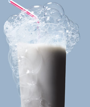 Tall glass of milk with big bubbles and striped straw