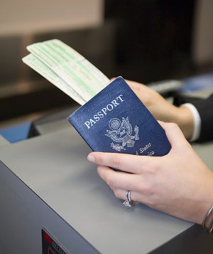 Woman's hands holding airline ticket and passport at check-in counter