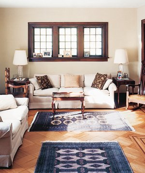 Room with a white couch and blue rug