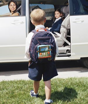 Young boy with a backpack walking towards a minivan