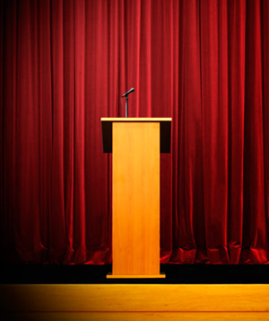 Empty podium in front of a red curtain
