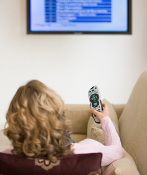 Woman with remote control watching television