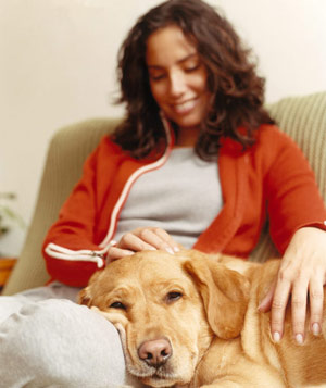 Woman relaxing on a couch with a dog