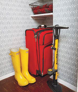 Suitcase, rubber boots and bike pump in corner of closet