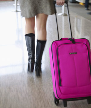 Woman pulling luggage through airport terminal