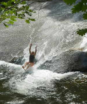 Person sliding down a rock waterfall at Pisgah National Forest, North Carolina