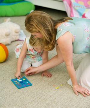Mother and daughter playing together in child's bedroom
