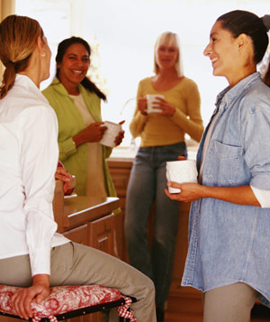 Women talking and having coffee in kitchen