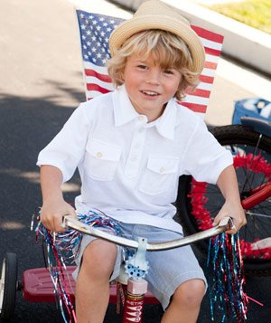 Young boy on tricycle with American flag and streamers