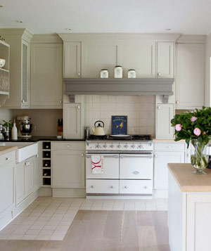 Cozy white kitchen with grey floors and roses on countertop