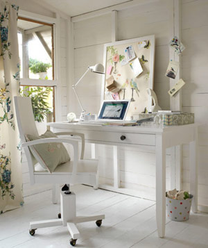 White home office with swivel chair and painted white wood floors