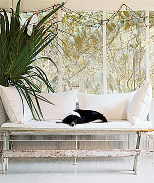 White enclosed porch, white bench with pillows and sleeping dog