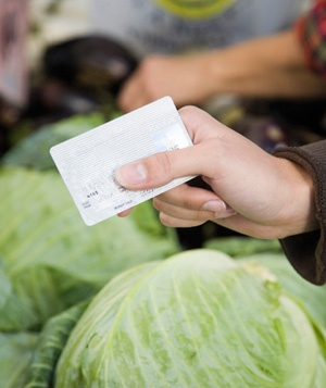 Person holding credit card over vegetables