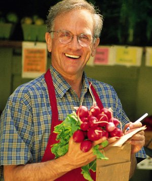 Man holding bunch of radishes at a farmers market