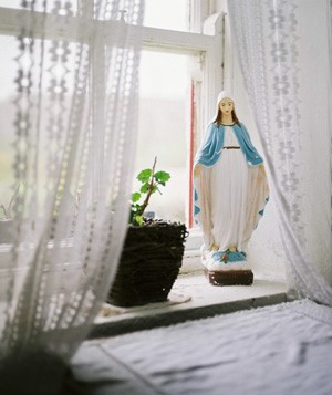 Small statue of Virgin Mary sitting on window sill