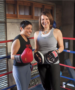 2 women wearing boxing gloves standing in a boxing ring