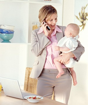 Business woman on phone holding baby