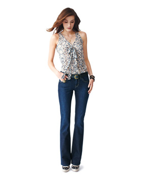 Model wearing ruffled white print top, bootcut jeans and loafers