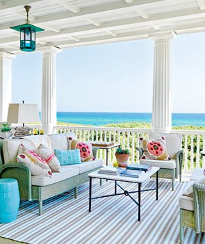 Open air covered deck with striped indoor-outdoor rug and seagrass rug