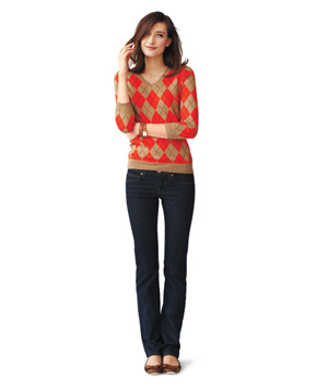 Model wearing argyle sweater, dark straight-leg jeans and flats
