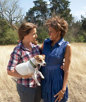 2 Women arm in arm standing in a brushy field with a small dog