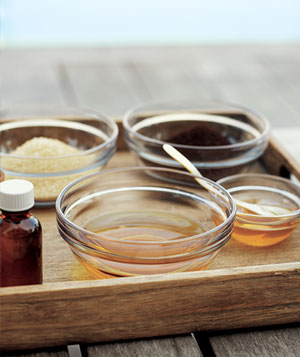 Glass bowls with various oils on a wooden tray outdoors