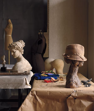Sewing room with head manniquins, fabric swatches, pins and beige fedora hat