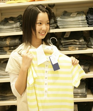 Teenage girl holding a t-shirt in a clothing store