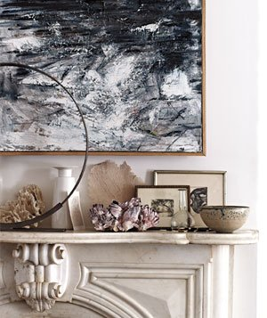 Grey marble mantel with framed artwork, vase, , bowl, sea plants and abstract painting on wall