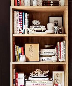 Wooden bookshelf with assorted books, photo, drawings, shells and white trinkets