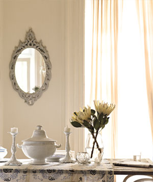 Elegant white dining room with china and glass table decroations, flowers in vase and mirror on wall