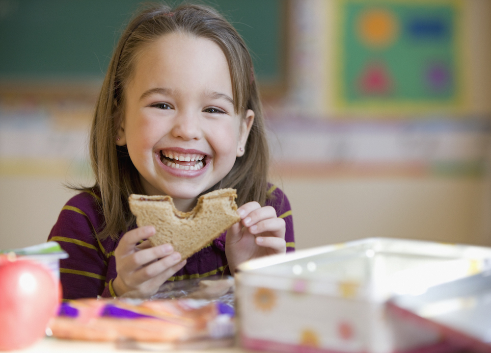 A Young Girl Eating Lunch at School