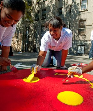 3 women painting big red smiley face in a parking lot, anniversary of 9/11 terrorist attacks