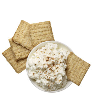 Triscuit crackers dipped in cottage cheese and garam masala